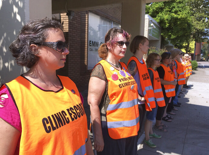 FILE - In this July 17, 2017 file photo, escort volunteers line up outside the EMW Women's Surgical Center in Louisville, Ky. Federal appeals judges were urged Thursday, Aug. 8, 2019, by an attorney for Kentucky's governor to restore a law at the heart of a licensing fight that threatened to close the state's last abortion clinic.  (AP Photo/Dylan Lovan, File)
