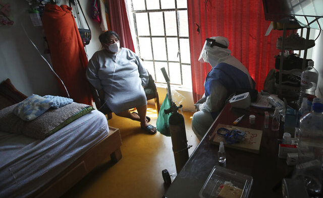 City worker Carlos Ruiz gives instruction to a COVID-19 patient after delivering a tank of oxygen to her home in the Iztapalapa borough of Mexico City, Friday, Jan. 15, 2021. The city offers free oxygen refills for COVID-19 patients. (AP Photo/Marco Ugarte)