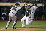 Oakland Athletics' Chris Herrmann, center, scores in front of New York Yankees' Austin Romine during the second inning of a baseball game Tuesday, Aug. 20, 2019, in Oakland, Calif. (AP Photo/Ben Margot)