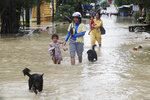 Villagers walk down a flooded dirt road following recent rains on the outskirts of Phnom Penh, Cambodia, Wednesday, Oct. 14, 2020. A Cambodian disaster official said Wednesday that more than 10,000 people have been evacuated to the safety places after the tropical storm hit the country by causing the flash flood. (AP Photo/Heng Sinith)