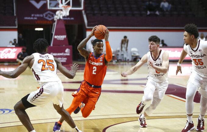 Clemson's Al-Amir Dawes, center, drives towards the basket in the second half of an NCAA  college basketball game in Blacksburg Va., Tuesday, Dec. 15, 2020.  (Matt Gentry/The Roanoke Times via AP, Pool)