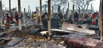 Rohingya refugees walk in the charred remains after a fire broke out in Nayapara Camp in Cox's Bazar district, Bangladesh, Thursday, Jan. 14, 2021. A fire raced through a sprawling Rohingya refugee camp in southern Bangladesh on Thursday, destroying hundreds of homes, officials said. No casualties were reported. The UNHCR said more than 550 homes sheltering about 3,500 people as well as 150 shops were either totally or partially destroyed in the fire. (AP Photo/Mohammed Faisal)