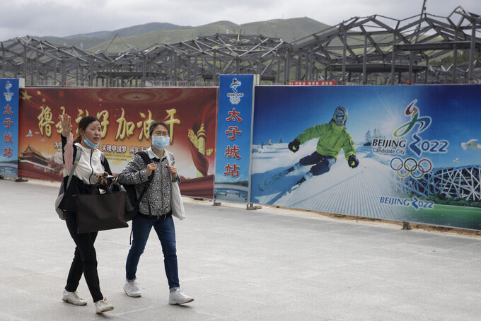 Visitors to Chongli, one of the venues for the Beijing 2022 Winter Olympics, past by billboards promoting the event in Chongli in northern China's Hebei Province on Monday, Aug. 17, 2020.  China's repression in Tibet, the status of the exiled Dalai Lama, and its treatment of ethnic minorities spurred violent protests ahead of Beijing's 2008 Olympics. It could happen again. China is host to the 2022 Winter Olympics with rumblings of a boycott and calls to remove the games from Beijing because of widespread human rights violations. (AP Photo/Ng Han Guan)