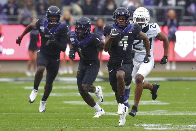 """FILE - In this Nov. 29, 2019, file photo, TCU wide receiver Taye Barber (4) carries the ball against West Virginia in an NCAA college football game in Fort Worth, Texas. Barber and his TCU teammates have been together on campus for more than three months, and now jump right into Big 12 play after having their only non-conference game wiped out because of COVID-19. """"Everybody has been itching to get back on the field,"""" said Barber, a junior receiver. (AP Photo/Richard W. Rodriguez, File)"""