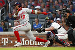 Washington Nationals' Victor Robles (16) follows through on a three-run double next to Atlanta Braves catcher Brian McCann during the third inning of a baseball game Thursday, July 18, 2019, in Atlanta. (AP Photo/John Bazemore)