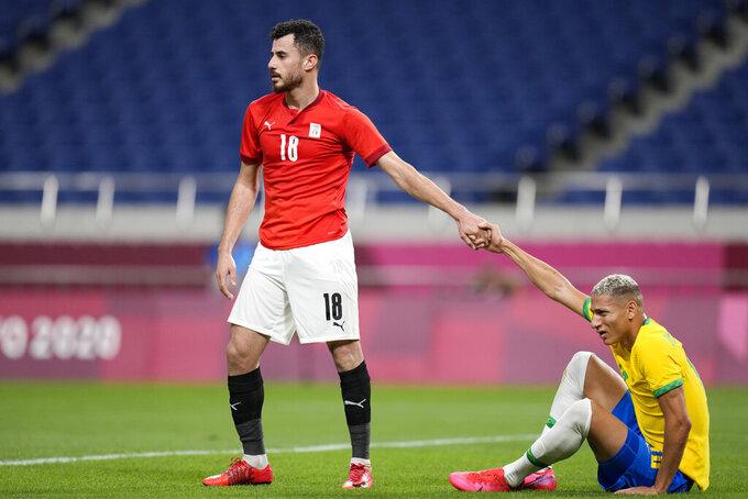 Egypt's Mahmoud El Wench, left, helps Brazil's Richarlison get up during a men's quarterfinal soccer match at the 2020 Summer Olympics, Saturday, July 31, 2021, in Saitama, Japan. (AP Photo/Silvia Izquierdo)
