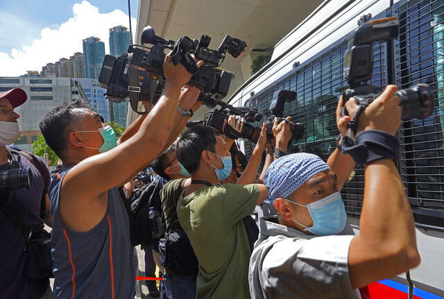 In this Monday, July 6, 2020, file photo, a police van is surrounded by press photographers at a court in Hong Kong. Hong Kong's professional journalism association on Thursday, Sept. 24, 2020, protested new rules restricting who can provide press coverage during demonstrations, saying the government has no right to determine who is or isn't a reporter. (AP Photo/Vincent Yu/ File)