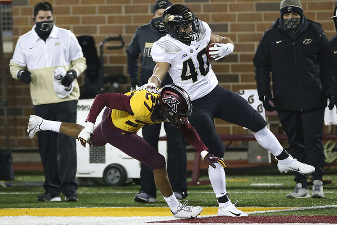 Purdue running back Zander Horvath (40) tries to stay in the field of play against Minnesota defensive back Tyler Nubin (27) during the first half of an NCAA college football game Friday, Nov. 20, 2020, in Minneapolis. (AP Photo/Stacy Bengs)
