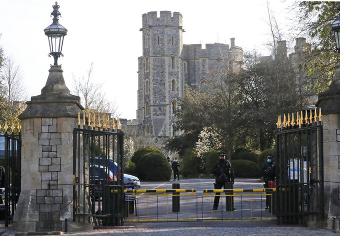 Armed police guards the entrance of Windsor Castle after the death of Britain's Prince Philip in Windsor, Sunday, April 11, 2021. Britain's Prince Philip, the irascible and tough-minded husband of Queen Elizabeth II who spent more than seven decades supporting his wife in a role that mostly defined his life, died on Friday. (AP Photo/Frank Augstein)