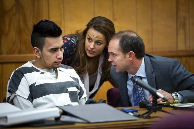 FILE - In this Nov. 14, 2019, file photo, Cristhian Bahena Rivera, left, talks to his defense attorney Jennifer Frese, center, through an interpreter during an evidence suppression hearing at the Poweshiek County Courthouse in Montezuma, Iowa. In a victory for prosecutors, a judge ruled Monday, Dec. 23, 2019, that they can use key evidence against Cristhian Bahena Rivera, who's charged with killing University of Iowa student Mollie Tibbetts. Judge Joel Yates agreed with prosecutors that some statements made by the suspect must be suppressed because they came during an interrogation after he was not fully read his legal rights. (Brian Powers/The Des Moines Register via AP, File)
