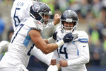 Tennessee Titans kicker Randy Bullock, right, celebrates with tight end Geoff Swaim, left, after Bullock kicked a field goal in overtime to give the Titans a 33-30 win over the Seattle Seahawks in overtime of an NFL football game, Sunday, Sept. 19, 2021, in Seattle. (AP Photo/John Froschauer)