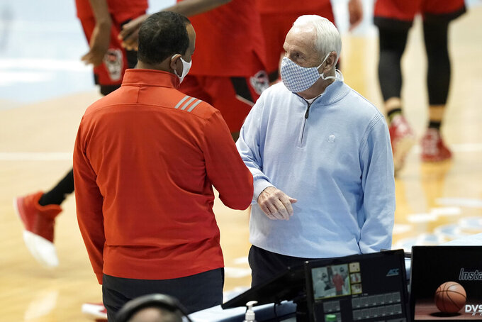 North Carolina State head coach Kevin Keatts, left, is greeted by North Carolina head coach Roy Williams prior to an NCAA college basketball game in Chapel Hill, N.C., Saturday, Jan. 23, 2021. (AP Photo/Gerry Broome)