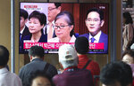 FILE - In this Thursday, Aug. 29, 2019 file photo, People watch a live TV screen showing a former South Korean President Park Geun-hye, left, her longtime confidante, Choi Soon-sil, and Samsung Group heir Lee Jae Yong, right, during a news program at the Seoul Railway Station in Seoul, South Korea. (AP Photo/Ahn Young-joon, File)