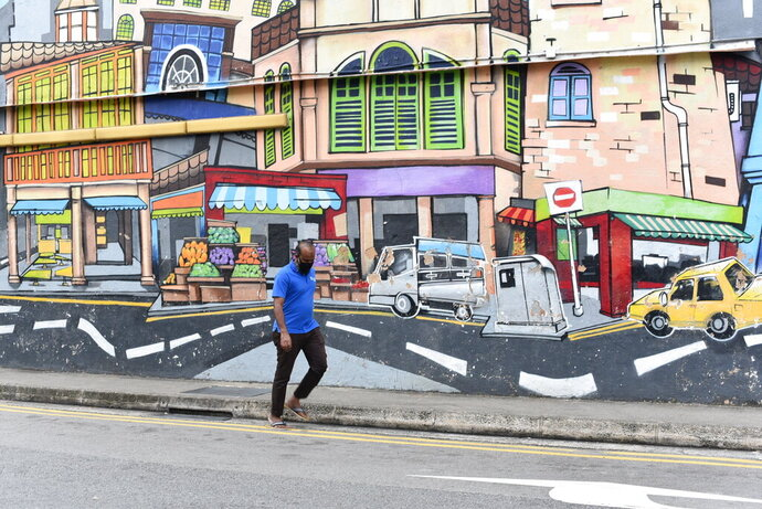 A man with a facemask walks past a wall mural in Singapore's Little India district on Saturday, May 16, 2020. Wearing of facemarks is mandatory for everyone who goes outside their homes to control the spread of the coronavirus in the city state. Singapore has reported more than 27,000 COVID-19 cases, with 90% of the cases linked to foreign workers dormitories, but it has a low fatality rate of 21 deaths. (AP Photo/YK Chan)