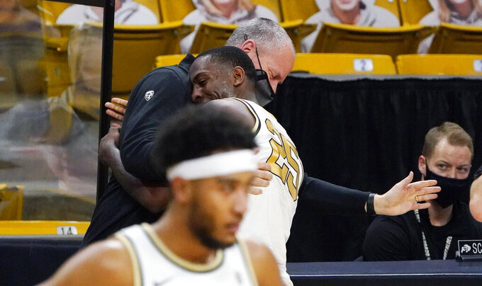Colorado guard McKinley Wright IV, front, is hugged by head coach Tad Boyle as he leaves the floor in the second half of an NCAA college basketball game against Arizona State, Thursday, March 4, 2021, in Boulder, Colo. (AP Photo/David Zalubowski)