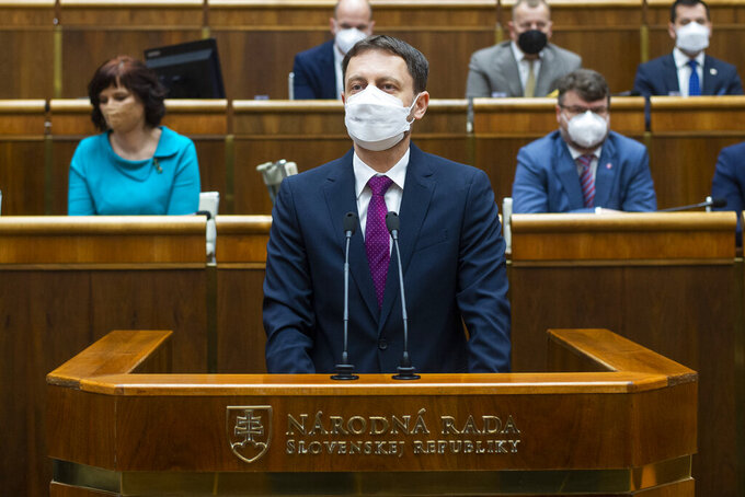 Slovakia Prime Minister Eduard Heger, addresses lawmakers in the parliament in Bratislava, Tuesday May 4, 2021.  Eduard Heger's Cabinet obtained a vote of confidence from Parliament on Tuesday. (Jakub Kotian / TASR via AP)