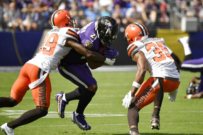 Baltimore Ravens running back Mark Ingram (21) runs with the ball as Cleveland Browns cornerback Terrance Mitchell (39) and defensive back Jermaine Whitehead (35) try to bring him down during the first half of an NFL football game Sunday, Sept. 29, 2019, in Baltimore. (AP Photo/Brien Aho)