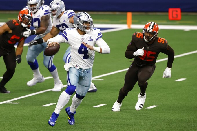 Dallas Cowboys quarterback Dak Prescott (4) scrambles out of the pocket before throwing a pass under pressure from Cleveland Browns defensive end Myles Garrett (95) in the first half of an NFL football game in Arlington, Texas, Sunday, Oct. 4, 2020. (AP Photo/Ron Jenkins)