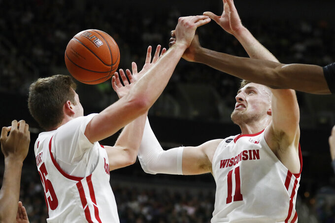 Wisconsin forwards Nate Reuvers (35) and Micah Potter (11) reach for a rebound during the first half of an NCAA college basketball game against Michigan State, Friday, Jan. 17, 2020, in East Lansing, Mich. (AP Photo/Carlos Osorio)
