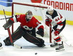 New Jersey Devils left wing Miles Wood (44) and Ottawa Senators goaltender Marcus Hogberg (35) keep their eyes on a loose puck during third period NHL hockey action in Ottawa on Monday, Jan. 27, 2020. (Fred Chartrand/The Canadian Press via AP)