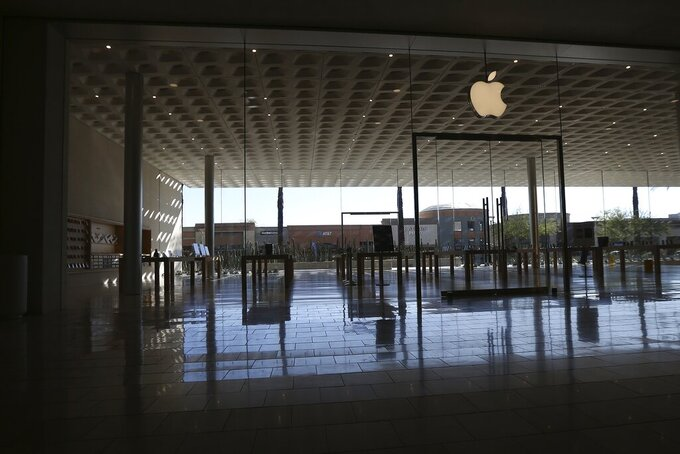 FILE - In this March 14, 2020 file photo, an Apple retail store is closed at a local mall  in Scottsdale, Ariz. Apple is temporarily closing 11 stores in Arizona, Florida, North Carolina and South Carolina just few weeks after reopening them in hopes that consumers would be able to shop in them without raising the risk of infecting them or company workers with the novel coronavirus that caused COVID-19. (AP Photo/Ross D. Franklin, File)
