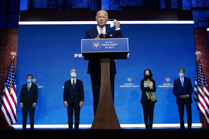 President-elect Joe Biden removes his face mask as he arrives to introduce his nominees and appointees to key national security and foreign policy posts at The Queen theater, Tuesday, Nov. 24, 2020, in Wilmington, Del. President-elect Joe Biden's first wave of Cabinet picks and choices for his White House staff have prized staying power over star power, with a premium placed on government experience and proficiency as he looks to rebuild a depleted and demoralized federal bureaucracy.(AP Photo/Carolyn Kaster)