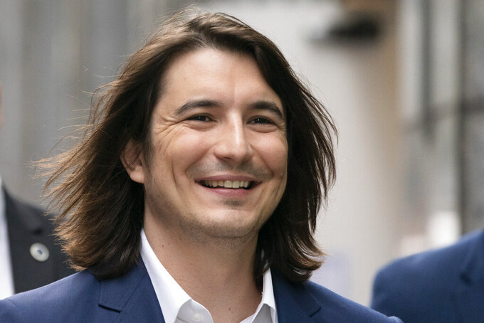 Vladimir Tenev, CEO and Co-Founder of Robinhood, walks in New York's Times Square following his company's IPO, Thursday, July 29, 2021. Robinhood is selling its own stock on Wall Street, the very place the online brokerage has rattled with its stated goal of democratizing finance. Through its app, Robinhood has introduced millions to investing and reshaped the brokerage industry, all while racking up a long list of controversies in less than eight years. (AP Photo/Mark Lennihan)
