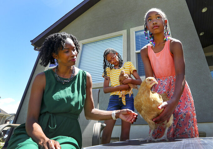 In this Wednesday, June 10, 2020 photo, In this Wednesday, June 10, 2020 photo Michelle Love-Day and two of her children,Elise Day, center, and Naomi Rose Day, look after two of their young chickens at their home in Bluffdale, Utah. (Steve Griffin/The Deseret News via AP)