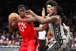 Toronto Raptors forward Pascal Siakam (43) keeps the ball from Brooklyn Nets forward Taurean Prince, right, and Nets center Jarrett Allen, center, rear, during the second quarter of an NBA basketball game, Wednesday, Feb. 12, 2020, in New York. (AP Photo/Kathy Willens)