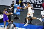 Texas' Donovan Williams, right, tries to keep the ball from going out of bounds as Abilene Christian's Damien Daniels, left, reaches for it during the first half of a college basketball game in the first round of the NCAA tournament at Lucas Oil Stadium in Indianapolis Saturday, March 20, 2021. (AP Photo/Mark Humphrey)