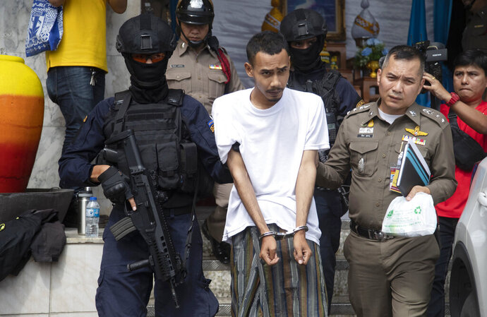 Police officers escort Lu-ai Saengae, center, one of suspects of planting two small bombs, as they leave Pathumwan police station to the criminal court in Bangkok , Thailand, Thursday, Aug. 15, 2019. A court in Thailand has extended the detention of two suspects accused of planting two small bombs in front of police headquarters in Bangkok while Southeast Asian foreign ministers were meeting nearby. (AP Photo/Sakchai Lalit)