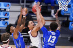 Gonzaga guard Jalen Suggs (1) drives between Creighton guard Shereef Mitchell, left, and Christian Bishop (13) in the first half of a Sweet 16 game in the NCAA men's college basketball tournament at Hinkle Fieldhouse in Indianapolis, Sunday, March 28, 2021. (AP Photo/Michael Conroy)