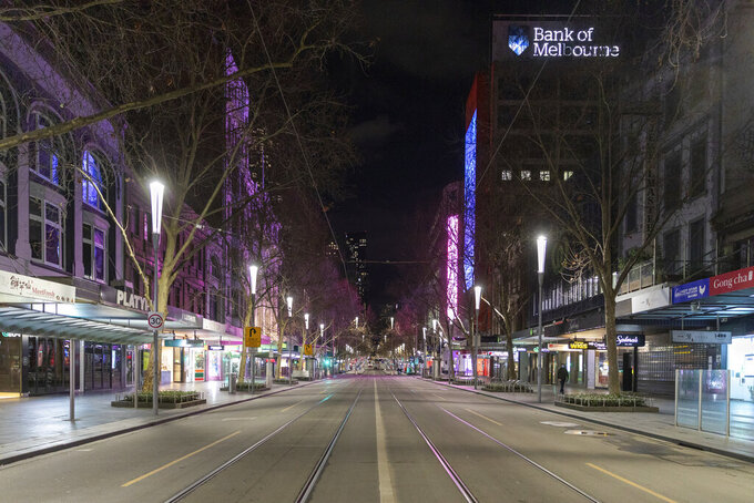 FILE - In this Aug. 5, 2021, file photo, an empty Swanston Street is seen at night in the Central Business District as lockdown due to the continuing spread of COVID-19 prepares to start in Melbourne. Melbourne, the city that was once Australia's worst COVID-19 hot spot has announced a seven-day lockdown, its fourth since the pandemic began. (AP Photo/Asanka Brendon Ratnayake, File)