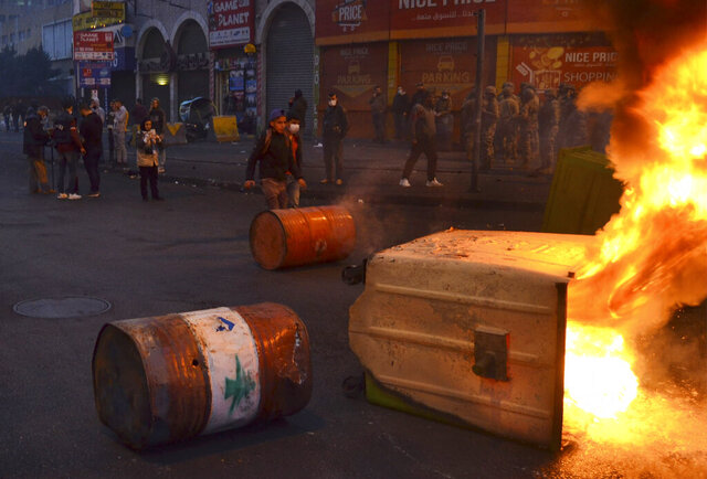 Lebanese protesters block a road with barrels and burned garbage containers during a protest against strict lockdown measures in Tripoli, north Lebanon, Tuesday, Jan. 26, 2021.  Lebanon has hit a new daily record for COVID-19 fatalities, as protesters took to the streets for a second day to denounce strict lockdown measures put in place to curb an exhausting surge in infections. (AP Photo)