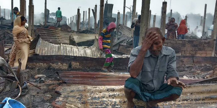 A Rohingya refugee sits by the charred remains after a fire broke out in Nayapara Camp in Cox's Bazar district, Bangladesh, Thursday, Jan. 14, 2021. A fire raced through a sprawling Rohingya refugee camp in southern Bangladesh on Thursday, destroying hundreds of homes, officials said. No casualties were reported. The UNHCR said more than 550 homes sheltering about 3,500 people as well as 150 shops were either totally or partially destroyed in the fire. (AP Photo/Mohammed Faisal)