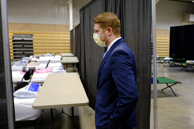 Brett Peppin, director of environmental health with Boone County Health Department, looks beds set-up in a building at the Boone County 4-H Fairgrounds to handle COVID-19 patients, Monday, April 6, 2020, in Lebanon, Ind. The new coronavirus causes mild or moderate symptoms for most people, but for some, especially older adults and people with existing health problems, it can cause more severe illness or death. (AP Photo/Darron Cummings)