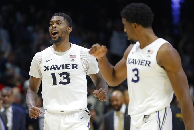 Xavier's Naji Marshall (13) celebrates the team's overtime win over Missouri in an NCAA college basketball game Tuesday, Nov. 12, 2019, in Cincinnati. (AP Photo/John Minchillo)