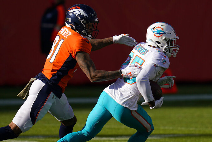 Miami Dolphins cornerback Xavien Howard (25) runs back an interception intended for Denver Broncos wide receiver Tim Patrick (81) during the first half of an NFL football game, Sunday, Nov. 22, 2020, in Denver. (AP Photo/David Zalubowski)
