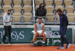 Spain's Rafael Nadal, center, coach Francisco Roig, right, and his staff wearing face masks to prevent the spread of coronavirus gather during a break at the Roland Garros stadium during practicing in Paris, Friday, Sept. 25, 2020. Already repeatedly trimmed, crowd sizes for the French Open have been reduced again to just 1,000 spectators per day because of the worsening coronavirus epidemic in Paris. (AP Photo/Michel Euler)