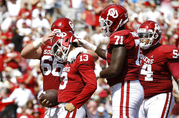 Oklahoma quarterback Caleb Williams (13) celebrates with offensive linemen Robert Congel (66) and Anton Harrison (71) after scoring a touchdown against Tulane during a NCAA college football game Saturday, Sept. 4, 2021, in Norman, Okla. (AP Photo/Alonzo Adams)