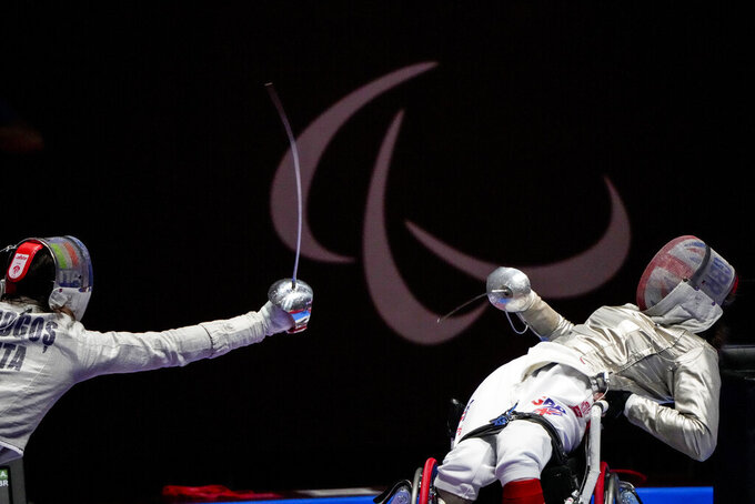 FILE - In this Aug. 25, 2021 file photo, Britain's Gemma Collins-McCann, right, defends against Italy's Ionela Andreea Mogos in women's saber individual, category A preliminary wheelchair fencing at the Tokyo 2020 Paralympic Games in Chiba, Japan. There are 4,403 Paralympic athletes competing in Tokyo, each with unique differences that have to be classified. Lines have to be draw, in the quest for fairness, to group similar impairments, or impairments that yield similar results. (AP Photo/Kiichiro Sato, File)