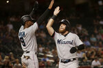 Miami Marlins' Austin Dean high-fives Lewis Brinson (9) after they scored on a hit by Miguel Rojas during the seventh inning of a baseball game against the Arizona Diamondbacks, Tuesday, Sept. 17, 2019, in Phoenix. (AP Photo/Matt York)