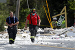 Firefighters walk through the scene of an explosion Monday, Sept. 16, 2019, in Farmington, Maine. Officials say a town's fire chief is among the injured in a propane explosion that killed a firefighter. State public safety spokesman Steve McCausland said after Monday morning's explosion at a nonprofit center in Farmington that multiple people remain hospitalized. (AP Photo/Robert F. Bukaty)