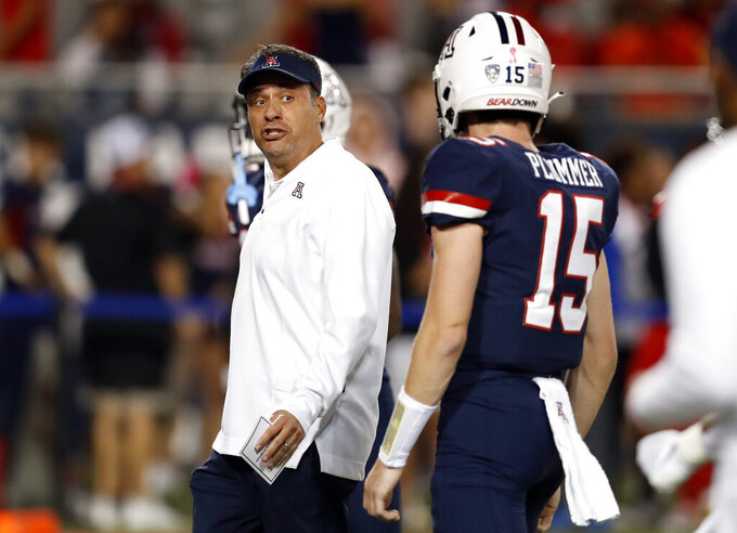 Arizona coach Jedd Fisch talks with quarterback Will Plummer (15) before the team's NCAA college football game against Washington on Friday, Oct. 22, 2021, in Tucson, Ariz. (AP Photo/Chris Coduto)