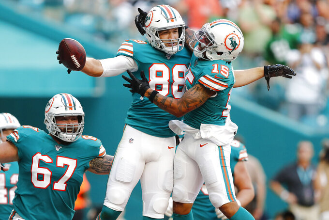 Miami Dolphins wide receiver Albert Wilson (15) congratulates tight end Mike Gesicki (88) after Gesicki scored a touchdown, during the second half at an NFL football game against the Philadelphia Eagles, Sunday, Dec. 1, 2019, in Miami Gardens, Fla. To the left is Miami Dolphins center Daniel Kilgore (67). (AP Photo/Brynn Anderson)