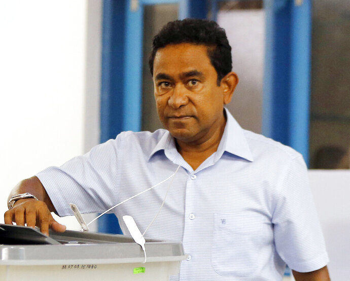 FILE - In this Sept. 23, 2018, file photo. then Maldivian President Yameen Abdul Gayoom casts his vote at a polling station during the presidential election in Male, Maldives. Police asked the Maldives' prosecutor general to charge Yameen with money laundering and his former Cabinet minister with aiding him. A police statement Wednesday night, Feb. 6, 2019, said that investigators have found grounds to charge Yameen and his former legal affairs minister. (AP Photo/Eranga Jayawardena, File)
