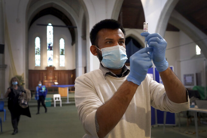 FILE - In this March 16, 2021, file photo, Pharmacist Rajan Shah prepares a syringe of the AstraZeneca vaccine at St John's Church, in Ealing, London. The global death toll from the coronavirus topped a staggering 3 million people Saturday, April 17, 2021, amid repeated setbacks in the worldwide vaccination campaign and a deepening crisis in places such as Brazil, India and France.  (AP Photo/Kirsty Wigglesworth, File)