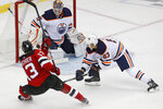 Edmonton Oilers goaltender Mikko Koskinen (19) blocks a shot by New Jersey Devils center Nico Hischier (13) with Oilers' Matt Benning (83) defending during the third period of an NHL hockey game Thursday, Oct. 10, 2019, in Newark, N.J. (AP Photo/Kathy Willens)