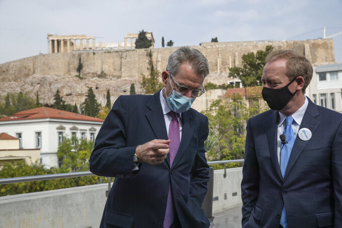 U.S. Ambassador to Greece Geoffrey Pyatt, left, speaks with Microsoft President Brad Smith, during a ceremony held in the Acropolis Museum, in the background the ancient Parthenon temple, in central Athens, on Monday, Oct. 5, 2020. Microsoft has announced plans to build three data centers in greater Athens, providing a badly needed investment of up to $1 billion to the Greek economy which has been hammered by the pandemic. (AP Photo/Petros Giannakouris)