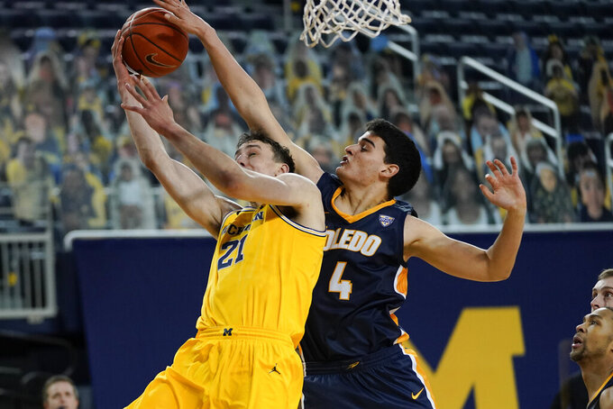 Toledo forward Mattia Acunzo (4) blocks a Michigan guard Franz Wagner (21) shot in the second half of an NCAA college basketball game in Ann Arbor, Mich., Wednesday, Dec. 9, 2020. (AP Photo/Paul Sancya)